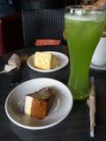 切片蓝莓乳酪蛋糕和提拉米苏蛋糕在白色陶瓷板材有高杯的绿色苹果汁饮料 免版税库存图片