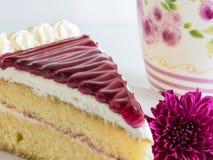 切片蓝莓蛋糕和紫罗兰色花,一杯茶,在软的焦点 库存照片