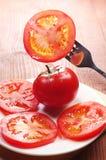 切片蕃茄在叉子和在板材 库存照片