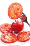 切片蕃茄在叉子和在板材 免版税库存图片