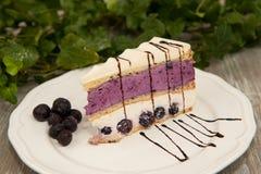 切片蛋糕用黑莓和白色巧克力在一块白色板材 免版税图库摄影