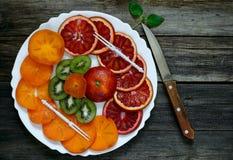 切片血橙、猕猴桃和柿子在一块白色板材和 图库摄影