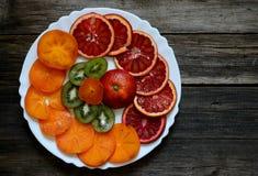 切片血橙、猕猴桃和柿子在一块白色板材和 免版税库存图片