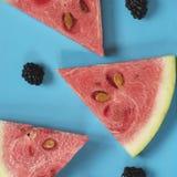 切片西瓜和黑莓在绿松石背景 免版税库存照片