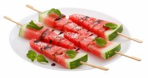切片西瓜用在白色板材的棍子在白色 库存图片