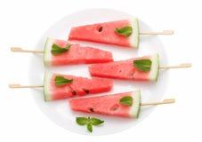 切片西瓜用在白色板材的棍子在白色 库存照片