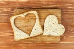 切片谷物与被删去的心脏的多士面包 库存图片