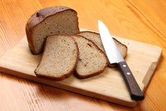 切片黑麦面包和一把厨刀在切板 库存照片