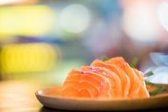 切的三文鱼生鱼片在木盛肉盘,日本食物可口菜单, bokeh与拷贝空间的迷离背景服务 免版税库存照片