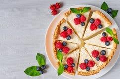 切的乳酪蛋糕用在白色板材的新鲜的莓果-健康有机点心 经典纽约乳酪蛋糕 免版税库存图片