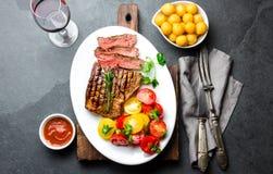 切的半生半熟烤牛排在白色板材服务用蕃茄沙拉和土豆球 烤肉, bbq肉 免版税库存图片