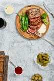 切的半生半熟烤牛排用红葡萄酒 免版税库存图片