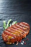 切的半生半熟烤牛排用调味汁、迷迭香和香料在石背景 免版税图库摄影