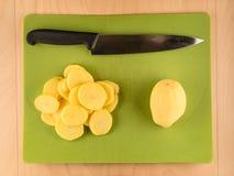 切的土豆和刀子在绿色塑料委员会 库存图片
