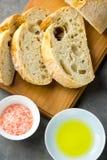 切的工匠土气面包顶视图在木切板的有盐和橄榄油的在黑暗的具体表上 金黄外壳 免版税库存照片