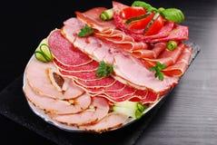 切的火腿、蒜味咸腊肠和被治疗的肉盛肉盘  库存照片
