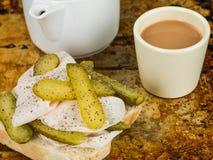 切的烘烤土耳其用嫩黄瓜腌制与一杯茶的单片三明治 库存照片