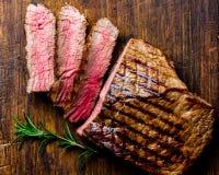 切的烤半生半熟牛排在木板烤肉, bbq肉牛里脊肉服务 顶视图,板岩 免版税库存照片