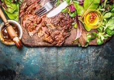 切的烤牛排服务用蔬菜沙拉、烤肉汁和利器在木毁坏的委员会和土气背景,顶视图 库存照片