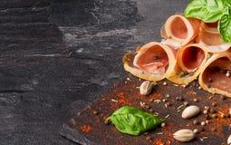 切的熏火腿和绿色蓬蒿的特写镜头图片在深灰背景离开 酒客的鲜美快餐 免版税库存照片