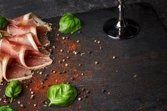 切的熏火腿和绿色蓬蒿的特写镜头图片在黑石背景离开 酒客的鲜美快餐 免版税库存照片