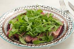 切的牛肉在与盐、胡椒和火箭的烤箱烹调了 免版税库存照片