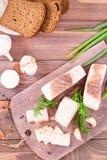 切的盐味的猪油用大蒜和莳萝在切板 库存照片