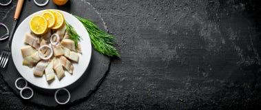 切的盐味的鲱鱼用莳萝、柠檬和洋葱圈 库存图片