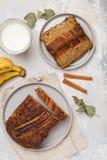切的素食主义者香蕉面包用在灰色板材的桂香 灰色bac 免版税库存图片