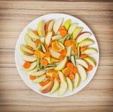 切的红萝卜、苹果、猕猴桃、蜜桔和桔子在白色 免版税库存图片