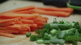 切的红萝卜和被切的春天葱在木切板 股票录像