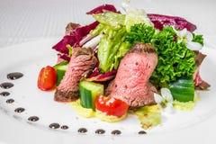 切的肉鲜美,开胃片断用调味汁,蕃茄、黄瓜和草本,在一块白色板材 水平的框架 图库摄影