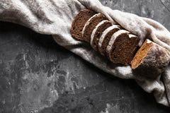 切的自创白色麦子面包用在老黑烤箱盘子的小麦面粉作为背景 顶视图 免版税库存图片