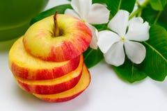 切的苹果用蔬菜汁和花 免版税库存图片