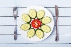 切的蕃茄和黄瓜健康早餐在白色板材 叉子和刀子在木桌上 顶视图 复制空间 库存照片