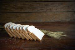 切的面包和麦子在木桌上 库存照片