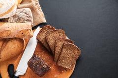 切的面包大面包在黑桌的 顶视图 库存图片