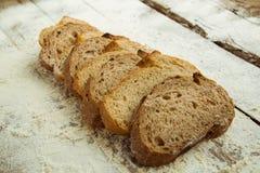 切的面包片在木桌上的用面粉 库存照片
