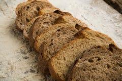 切的面包片在木桌上的用面粉 免版税库存图片