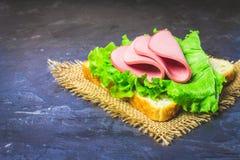 切的香肠用在面包片的莴苣 灰色大理石bac 免版税图库摄影
