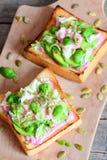 切的鲕梨、南瓜籽、莴苣、蓬蒿和甜菜根在一个木板的面包多士自创单片三明治调味 库存图片