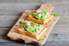 切的鲕梨、南瓜籽、莴苣、蓬蒿和甜菜根在白色在一个木板的多士自创单片三明治调味 免版税库存图片