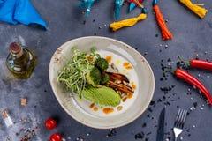 切的鲕梨用硬花甘蓝、发芽的麦子和烤南瓜在一个白色葡萄酒碗在石背景 图库摄影