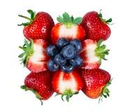 切的水多的草莓用蓝莓 背景查出的白色 图库摄影