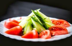 切的黄瓜和蕃茄和菜在板材 免版税库存照片