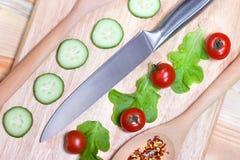 切的黄瓜,西红柿,在木切板的香料 健康概念的食物 免版税库存图片