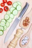 切的黄瓜,西红柿,在木切板的香料 健康概念的食物 免版税库存照片