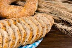 切的整粒面包用芝麻百吉卷 库存照片