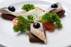 切的黑面包和鲱鱼在一块白色板材 图库摄影