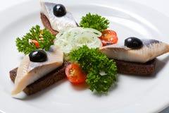 切的黑面包和鲱鱼在一块白色板材 免版税库存照片